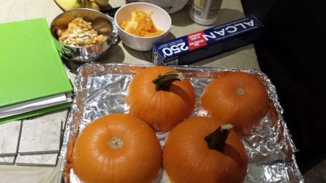 Here we see the pumpkins cut and on the baking sheet. Two bowls at the top have pumpkin guts (right) and pumpkin seeds (left).